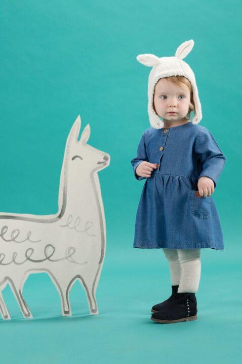 Staunendes stehendes Baby Mädchen trägt weiße warme gefütterte Baby Mütze mit Lama Ohren & verstellbaren Ohrenklappen Hasenohren - blaues Langarmkleid mit Taschen, Holz Knöpfen & Leder-Patch im Jeans Style Blue Denim - graue Strumpfhose - marine blaue Winter Babyschuhe von Pinokio - Babyphoto