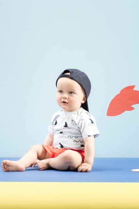 Sitzender Junge trägt blauen Baby Body kurzarm mit Haie Haifischflossen Ocean Meer Maritim Motive - Sommer rote kurze Short Hose aus Baumwolle mit Patch & elastischen Gummizugbund mit Kordel - Blaue Baby Mütze Baseball Cap Kinder von Pinokio - Babyphoto