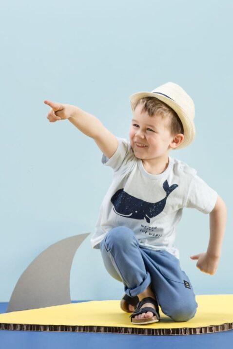 Knieender lachender Junge trägt hellblaues T-Shirt Babyshirt mit Wal Meer Motiv - Blaue Baby lange Hose Baumwollhose Schlupfhose Sweathose mit Taschen & Kordel Komfortbund & Patch - Beiger Strohhut - Blaue Kindersandalen von Pinokio - Kinderphoto