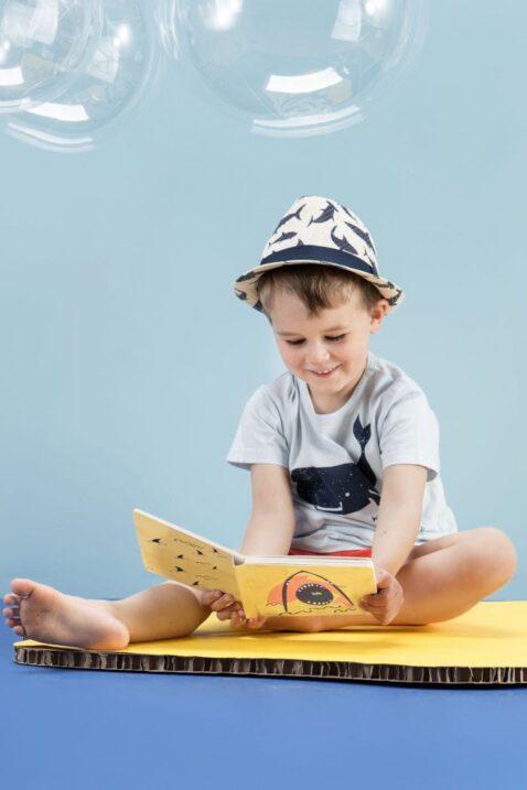 Sitzender Junge liest ein Buch & trägt hellblaues Baby Basic T-Shirt Babyshirt mit Wal Meer Motiv - Sommer rote kurze Shorts Hose aus Baumwolle mit Patch Save the world & elastischen Gummizugbund mit Kordel - Blau weißer Baby Sommerhut - Kinderphoto