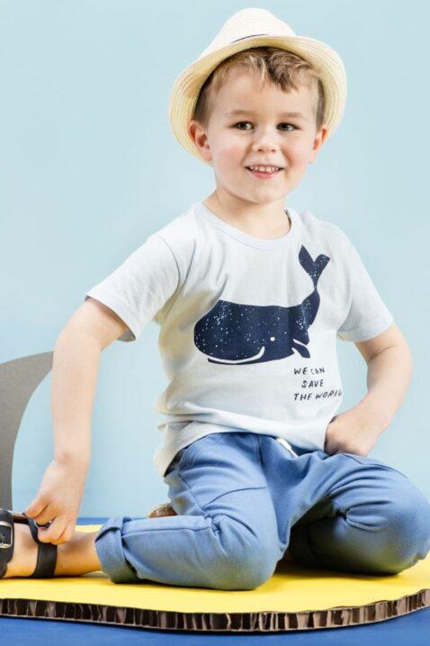 Sitzender Junge trägt blaues Baby T-Shirt mit Wal Meer Motiv - Marineblaue Baby Sommer Hose Sweathose Schlupfhose lang mit Taschen vorne, Kordel Gummizug & Patch - Beigen Strohhut - dunkelblaue Sandalen von Pinokio - Kinderphoto