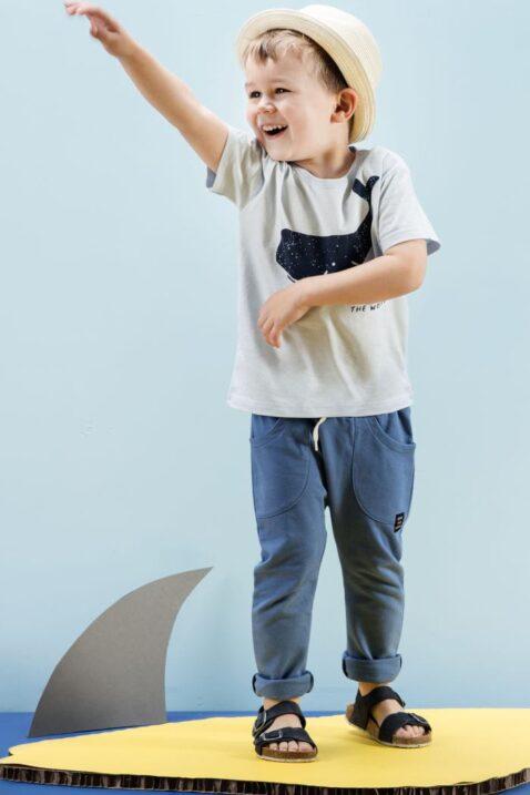 Stehender lachender Junge trägt blaues Babyshirt T-Shirt mit Meer Wal Motiv - Navyblaue Baby lange Schlupfhose Sommerhose Sweathose mit vorderen Taschen & Kordel Gummizug & Patch - Strohhut beige - dunkelblaue Kinder Sandalen von Pinokio - Kinderphoto
