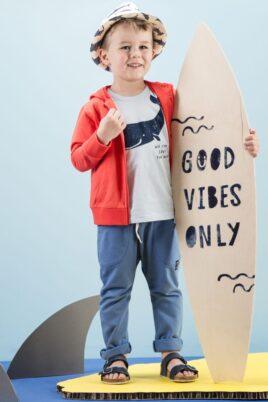 Junge mit Surfbrett trägt hellblaues T-Shirt Babyshirt mit Wal Meer Sommer Motiv - Rote Sweatjacke Kapuzenpullover Oberteil mit Reissverschluss & Patch - Lange blaue Babyhose mit Taschen - Strohhut & blaue Kinder-Sandalen von Pinokio - Kinderphoto