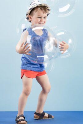 Lachender Junge trägt rote kurze Shorts Babyhose mit Patch - Blaues ärmelloses T-Shirt Tank-Top Trägertop Achselshirt im Jeans-Look - Blau-weißer Strohhut & blaue Kindersandalen von Pinokio - Kinderphoto