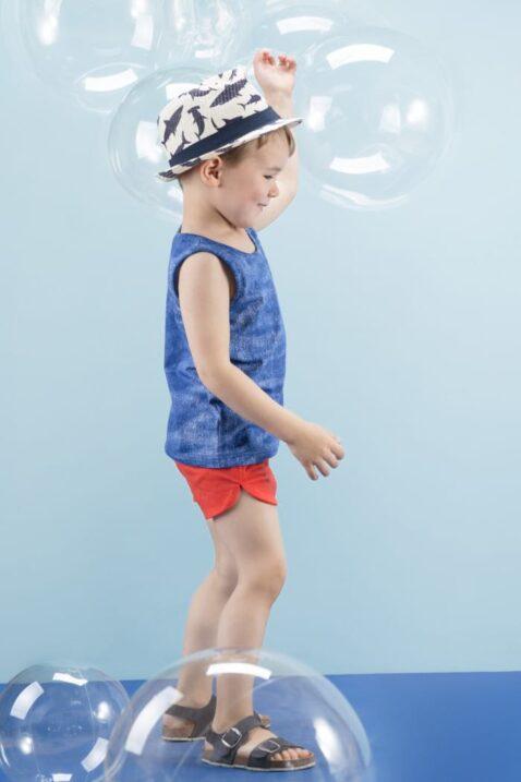 Spielender Junge trägt blaues Kinder T-Shirt ärmellos Tank-Top Muskelshirt im Jeans-Look - Rote kurze Sommer Kindershorts Baby-Hose mit Patch - Blaue Kinder-Sandalen & Strohhut Sommerhut von Pinokio - Kinderphoto