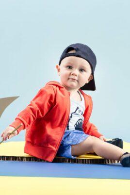 Sitzender Junge trägt blaue Baby Sommer Shorts im Jeans-Look mit Patch - Rote Kinder Kapuzen-Sweatjacke mit Reissverschluss - Hellblaues Tank-Top ärmellos mit Hai Wal - Blaue Baseball Cap Mütze von Pinokio - Babyphoto