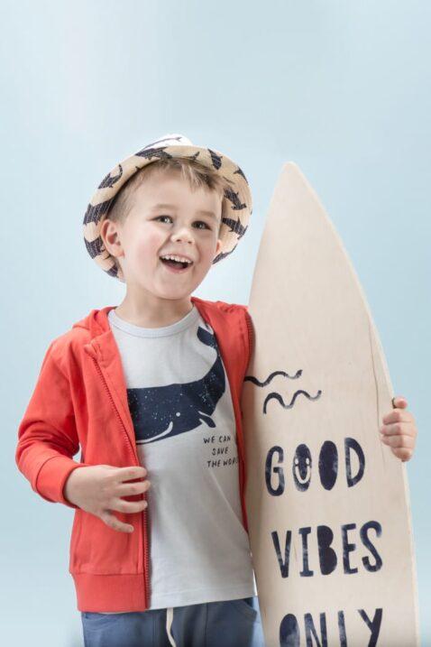 Lachender Junge mit Surfbrett trägt rote Baby Kinder Kapuzen-Sweatjacke mit Reissverschluss & Patch - Blaues T-Shirt mit Wal Motiv - Lange blaue Babyhose & Strohhut blau-weiss von Pinokio - Kinderphoto