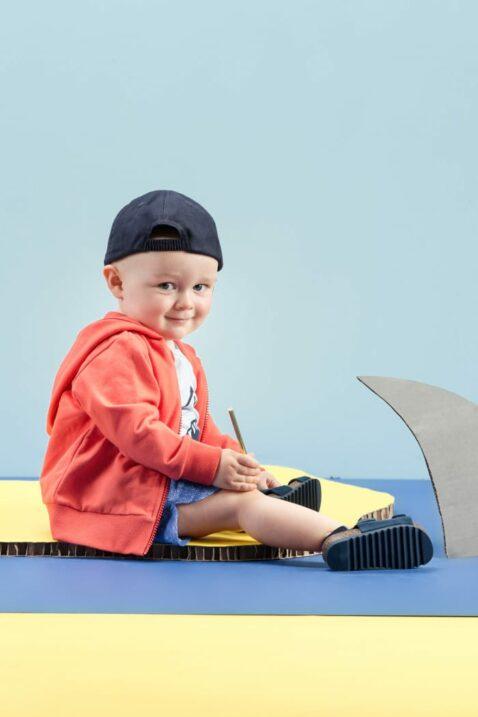 Sitzender Junge trägt blaues Baby kurzarm T-Shirt Babyshirt mit Wal - Sweatjacke Kapuzenpullover mit Patch in Rot - Kurze Shorts im Jeans-Look Sommerhose - Marineblaue Baseball Cap & Baby Sandalen navyblau von Pinokio - Babyphoto