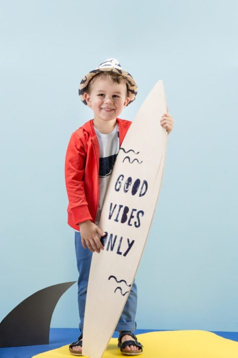 Stehender Junge mit Surfbrett trägt blaues Babyshirt kurzarm T-Shirt mit Wal Motiv - Rote lange Sweatjacke mit Kapuze - Lange blaue Sweathose Babyhose für den Sommer - Heller Strohhut & Kindersandalen marineblau - Kinderphoto