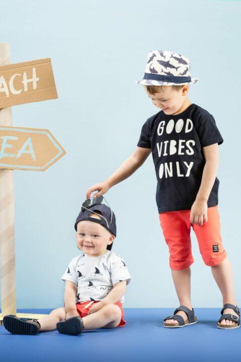 Zwei Kinder Jungs am Strand - Baby Junge trägt blauen Body kurzarm mit Hai Motiven mit roter kurzer Shorts & blauer Baseball Cap - Größere Junge Kind trägt dunkelblaues Statement T-Shirt mit roter kurzer Hose & Sommer Strohhut von Pinokio - Kinderphoto