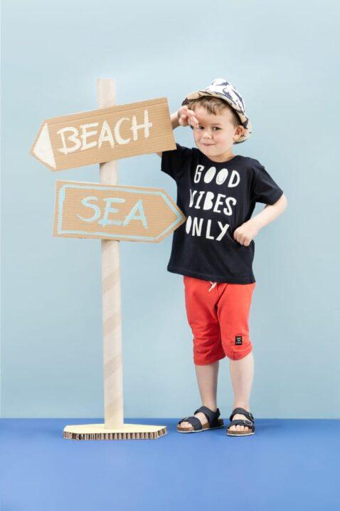 """Stehender Junge trägt blaues Kinder Statement T-Shirt """"GOOD VIBES ONLY"""" mit Smiley kurzarm - Rote kurze Hose knielang mit Patch & Kordel Sweathose Sommerhose - Heller Sommerhut & marineblaue Kinderschuhe von Pinokio - Kinderphoto"""