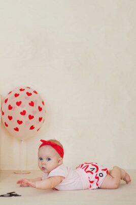 Krabbelndes Baby Mädchen trägt rosa kurze Windelabdeckung Bloomer mit LOVE Buchstaben Wellen Schleifen - Rosa Baby Sommer Body Wickelbody LOVE kurzarm kurze Ärmel - Rotes Stirnband mit Schleife von Pinokio - Babyphoto