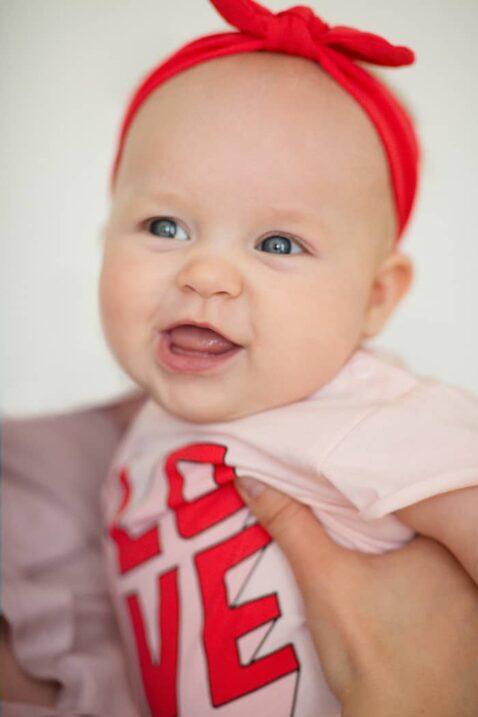 Lachendes Baby Mädchen Kind auf dem Arm der Mutter trägt rosa Body Wickelbody kurzarm kurze Ärmel im LOVE & LIEBE 3D Buchstaben Design Oberteil - Rotes Stirnband mit Schleife Erstlingsoutfit von Pinokio - Babyphoto