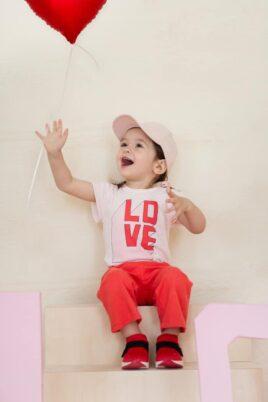Lachendes Baby Mädchen Kind mit Luftballon trägt rosa Kurzarmbody LOVE & LIEBE im 3D Buchstaben Design Oberteil - Rote Sommer 7/8 Babyhose mit Schleife Zierschleife - Rosa Baseball-Cap & rote Sneaker von Pinokio - Babyphoto