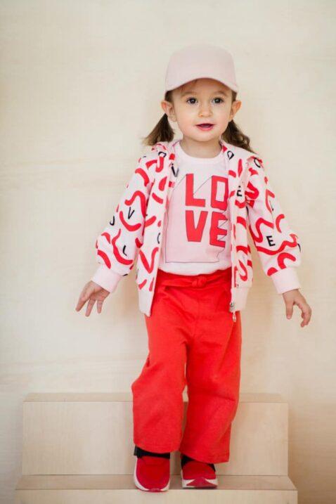 Mädchen Kind trägt rote Sommer 7/8 Babyhose mit Schleife & weitem Bein - Rosa Sommer Body kurzarm Love Design - Rosa Love Zip Kapuzen-Sweatjacke mit Reißverschluss & rosa Baseball Cap von Pinokio - Kinderphoto