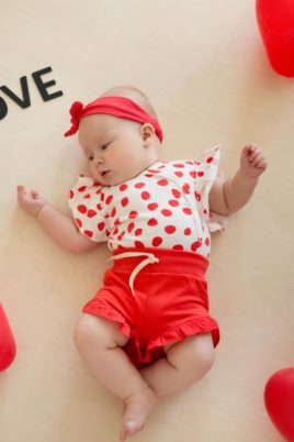 Liegendes Mädchen Baby trägt rote kurze Shorts Hose mit Rüschen & Kordel für den Sommer - Weiß rot gepunkteter Love Rüschen Wickelbody - Rotes Stirnband mit Schleife von Pinokio - Babyphoto