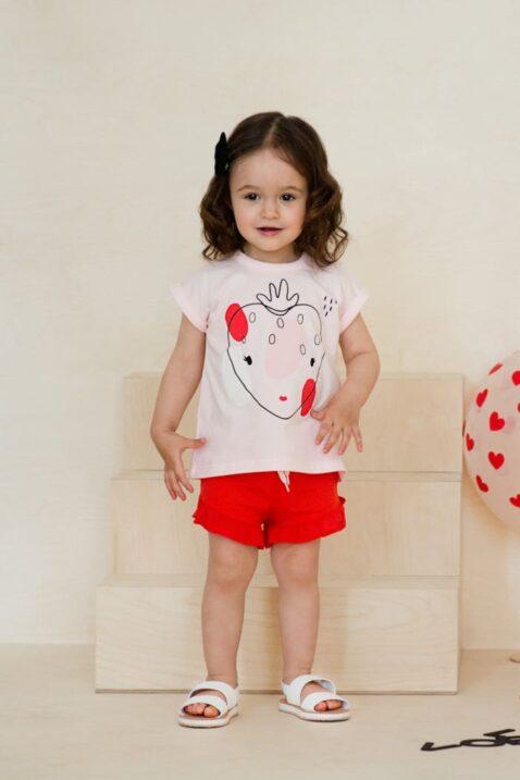 Stehendes lachendes Mädchen Kind trägt kurze rote Shorts Hose mit Rüschen & Kordel - Rosa kurzarm Sommer T-Shirt mit Erdbeer-Motiv Rundhals - Weiße Badesandalen von Pinokio - Kinderphoto