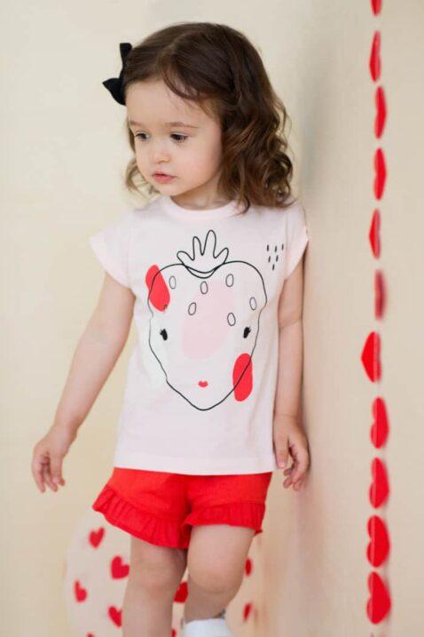 Stehendes Mädchen Kind trägt rosa T-Shirt kurzarm Sommershirt mit Erdbeer Motiv - Rote Shorts kurze Hose mit Rüschen & Kordel aus Baumwolle Sommershorts von Pinokio - Kinderphoto