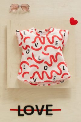 Rosarotes Baby T-Shirt LOVE & LIEBE Tunikaform Buchstaben Wellen Schleifen in Rot für Kinder Mädchen - Rosa rotes kurzes Babyshirt Sommer Oberteil Tunika in Baummwolle unifarben von Pinokio - Inspiration Lookbook