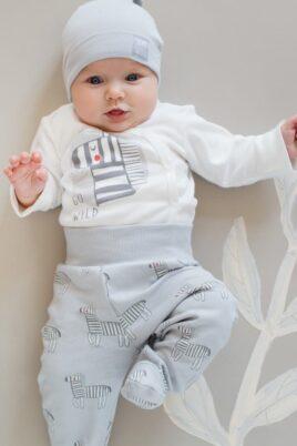 Liegender Baby Junge trägt weißen Wickelbody langarm mit Zebra - Graue Strampelhose mit Fuß, breiter Komfortbund & Zebras Schlafhose - Hellblaue Babymütze mit GO WILD Patch Kinder Baumwollmütze von Pinokio - Babyphoto