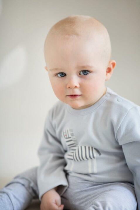 """Sitzender Junge trägt grauen Baby Langarmbody Body langarm mit Zebra Motiv & Zoo Schriftzug """"wild and free"""" - Hellgraue Leggings Babyhose Schlupfhose von Pinokio - Babyphoto"""