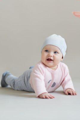 """Krabbelndes lachendes Mädchen trägt rosa Baby Langarmbody Body langarm mit Elefant - Hellgraue Sweathose Leggings Schlupfhose - Graue Kinder Babymütze mit Umschlag & Patch """"GO WILD"""" von Pinokio - Babyphoto"""