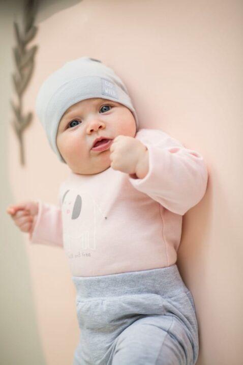 """Liegendes Baby Mädchen trägt rosa Babybody langarm Langarmbody mit Elefant - Graue Basic Leggings Sweathose Schlupfhose - Hellgraue Kinder Babymütze mit Umschlag & Patch """"GO WILD"""" von Pinokio - Babyphoto"""