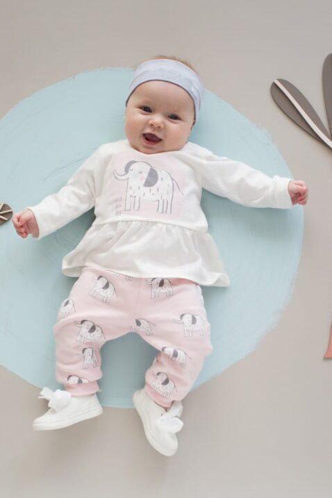"""Lachendes liegendes Baby Mädchen trägt rosa Leggings Sweathose mit Elefanten - Langarmshirt in Kleidchenoptik Tunika mit Elefant - Graues Stirnband mit Patch """"GO WILD"""" - Weiße Babyschuhe mit Schleife von Pinokio - Babyphoto"""