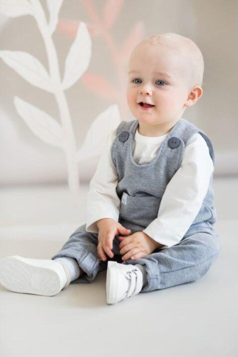Lachender sitzender Baby Junge trägt graue Baby Latzhose Trägerhose mit Tiger Patch, kleiner Brusttasche & Beinumschlag - Weißes Langarmshirt mit Zebra Motiv - Weiße Klettverschluss Babyschuhe von Pinokio - Babyphoto