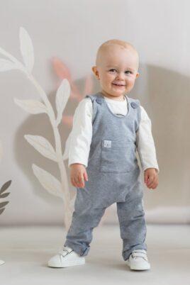Strahlender stehender Baby Junge trägt graue Baby Latzhose Sweathose Overall mit Tiger Patch, Beinumschlag, kleine Brusttasche - Langarmshirt mit Zebra in Weiß - Weiße Klettverschluss Babyschuhe von Pinokio - Babyphoto