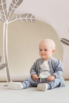 Sitzender Junge trägt graue Baby Pumphose Sweatpants Haremshose mit Taschen, Kordel & Bündchen - Graue Sweatjacke mit Tiger Patch & Reißverschluss - Weißes Langarmshirt mit Zebra Motiv von Pinokio - Babyphoto