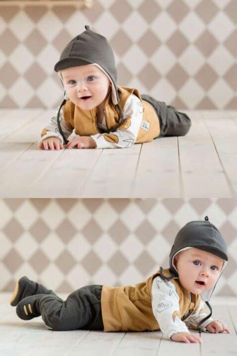 Krabbelnder Junge trägt braune Babymütze Oldtimer - Graue Leggings Sweathose Let´s Go - Braune Weste mit Tasche & Patch let´s Go im Sportwagen Oldtimer Rennwagen Look - Weisses Langarmshirt & graue Schlupfschuhe Hausschuhe von Pinokio - Babyphoto