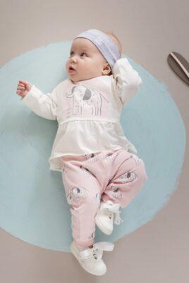 """Liegendes Baby Mädchen trägt rosa Sweathose Leggings mit Elefanten - Baby Langarmshirt rosa in Kleidchenoptik Tunika mit Elefant - Graues Stirnband Haarband Basic mit Patch """"GO WILD"""" - Weiße Babyschuhe mit Schleife von Pinokio - Babyphoto"""