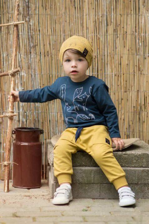 Sitzender Junge trägt currygelbe Babyhose mit Taschen, Kordel & Patch - Blaues leichtes Baby Langarmshirt & gelbe Babymütze mit Füchse, Wald Blätter, Eicheln - Weiße Babyschuhe mit Klettverschluss von Pinokio - Babyphoto Kinderphoto