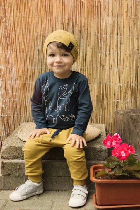 Sitzender Junge trägt gelbe Baby Pumphose mit Taschen - Dunkelblaues Babyshirt langarm & Baby Mütze mit Wald Blätter, Tiere, Füchse & Eicheln - Weiße Babyschuhe von Pinokio - Babyphoto Kinderphoto