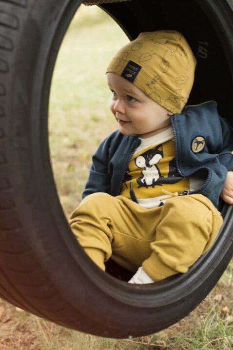 Spielender Junge trägt gelbe Babyhose mit Taschen & Patch - Currygelbe Babymütze mit Wald Blätter, Tiere Füchse & Eicheln - Dunkelblaue Fuchs Patch Sweatjacke mit Taschen & Streifen - Weißer Body mit Fuchs Motiv von Pinokio - Babyphoto