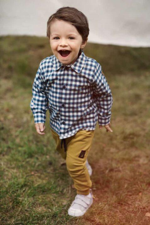 Staunender Junge trägt senfgelbe Baby Haremshose Pumphose mit Taschen, Kordel & Patch - Blau weiß kariertes Hemd Karohemd langarm - Weiße Babyschuhe mit Klettverschluss von Pinokio - Babyphoto Kinderphoto