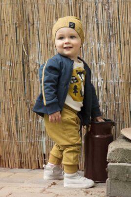 Stehender Junge trägt gelbe Baby Pumphose mit Taschen & Patch - Senfgelbe Babymütze mit Füchse, Blätter, Wald Eicheln - Blaue Sweatjacke mit Taschen, Streifen & Fuchs Patch - Weißer Body mit Fuchs von Pinokio - Babyphoto