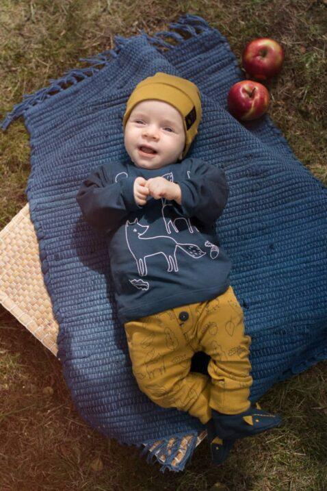 Lachender Junge trägt gelbe Baby Leggings Babyhose mit Füchse, Eulen, Blätter & Eicheln - Blaues Fuchs Langarm Oberteil - Senfgelbe Baby Mütze mit Patch Secret Forest- Blaue Fuchs Hausschuhe mit Ohren von Pinokio - Babyphoto