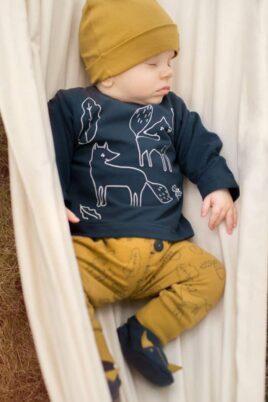 Schlafender Junge trägt gelbe Baby Leggings Sweathose mit Füchse, Kauz, Blätter & Eicheln - Blaues Langarmshirt - Gelbe Babymütze mit Patch Secret Forest- Blaue Schlupfschuhe Fuchs & Ohren von Pinokio - Babyphoto