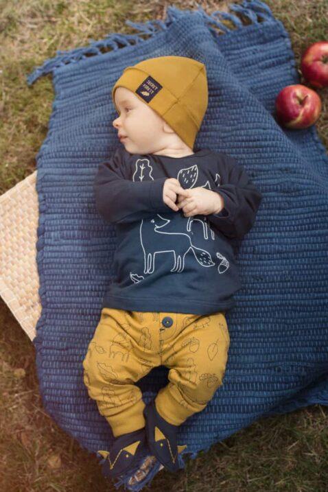 Liegender Junge trägt gelbe Baby Sweathose Leggings mit Füchse, Eulen & Eicheln - Marineblaues Langarmshirt Fuchs & Blätter - Currygelbe Babymütze mit Forest Patch - Blaue Fuchs Babyschuhe mit Ohren - Babyphoto