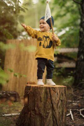 Lächelnder Junge mit Fahne im Wald trägt blaue Baby Leggings mit Knöpfe, Eichel & Blatt - Oversize Sweatshirt Fuchs Pullover in Gelb - Babymütze in Blau mit Patch von Pinokio - Kinderphoto Babyphoto
