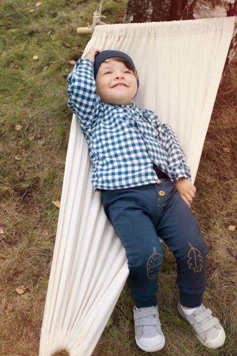 Lächelnder Junge in Hängematte trägt blaue Baby Leggings Schlupfhose mit Knöpfe, Eichel, Blatt - Blaues kariertes Herbst Winter Hemd mit Fuchs Patch - Baby Mütze in Blau mit Patch von Pinokio - Kinderphoto Babyphoto