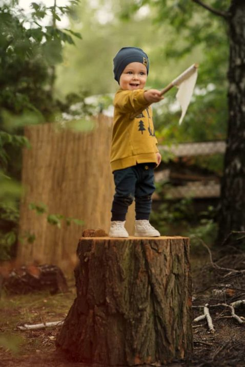 Lächelnder Junge auf einem Baumstamm trägt gelbes Baby Sweatshirt Oversize mit Zierknöpfe & Fuchs Motiv - Blaue Leggings mit Eichel & Blatt - Dunkelblaue Babymütze mit Patch von Pinokio - Kinderphoto Babyphoto