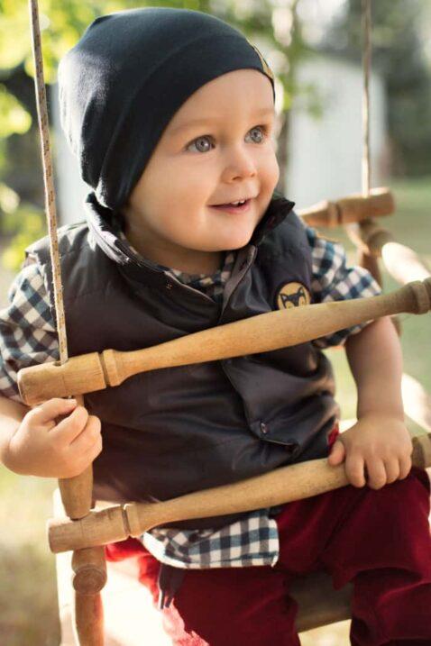 Spielender Junge in einer Babyschaukel trägt blaue Babymütze Kindermütze mit Fuchs Patch - Steppweste mit Fuchs Patch in Dunkelblau - Kariertes Hemd aus Baumwolle & Wolle in navy-weiß von Pinokio - Kinderphoto Babyphoto