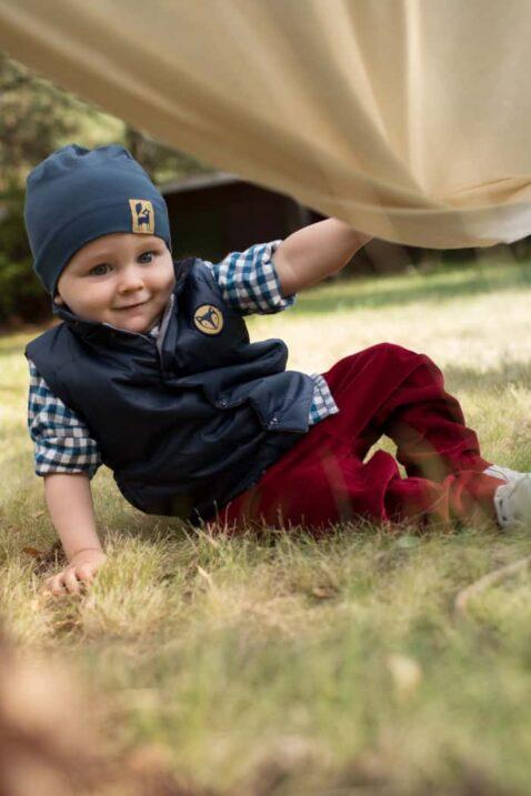 Sitzender Junge im Gras trägt gesteppte marineblaue Baby Weste mit Patch & Knöpfen - Karohemd Blau-weiss mit rundem Patch - Baby Mütze in navyblau mit gelbem Fuchs Patch von Pinokio - Kinderphoto Babyphoto