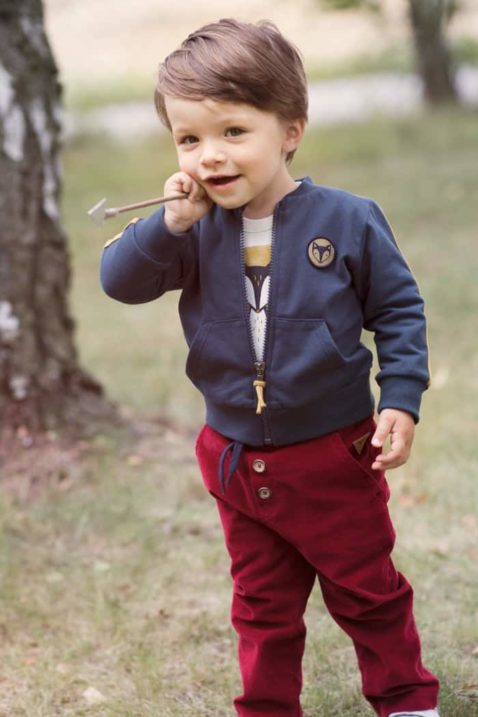 Baby Kind Junge mit Pfeil in der Hand trägt blaue Sweatjacke mit Streifen & Taschen - Weißen Langarmbody mit Fuchs - Bordeaux Rote Babyhose Cordhose mit dekorativen Knöpfen, Taschen, Fuchs Patch, Gummizug & Kordel Schnüre von Pinokio - Babyphoto Kinderphoto