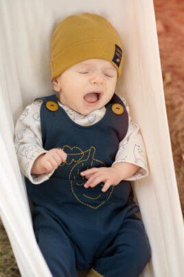 Schlafendes Baby trägt blaue Latzhose mit gestickter Eichel - Mütze mit Umschlag & Blatt Patch in Currygelb - Weisses Oberteil Cardigan Body mit Füchse, Blätter, Kauz & Uhus von Pinokio - Babyphoto
