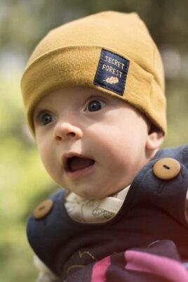 Junge trägt currygelbe Babymütze mit Umschlag & Patch SECRET FOREST - Blaue Latzhose mit Eichel - Weisser Wickelbody mit Fuchs, Uhus, Kauz von Pinokio - Babyphoto