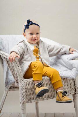 Lachendes Mädchen trägt weißen Baby Langarmbody mit Papagei - Currygelbe Babyhose mit Knöpfe - Beige Kinder Plüschjacke mit Kapuze & Reißverschluss von Pinokio - Babyphoto